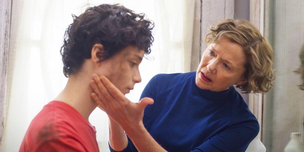 Annette Bening examines Lucas Jade Zumann.